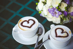 Cappuccino with hearts. Hot cappuccino on the table with flowers Royalty Free Stock Photos
