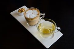 Cappuccino with hot tea and biscuit Royalty Free Stock Images