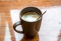 Cappuccino i brun kopp på trätabellen Arkivbilder