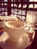 Cappuccino i szkło woda na stole Fotografia Stock