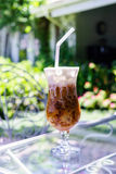 Cappuccino ice in coffee shop garden. Cappuccino ice on glass table in coffee shop garden royalty free stock photos