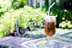 Cappuccino ice in coffee shop garden. Cappuccino ice on glass table in coffee shop garden stock photo