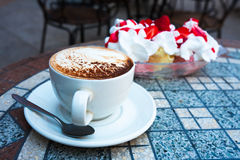 Cappuccino and Ice Cream. Cappuccino in white cup on table in cafe with ice cream in background royalty free stock photography