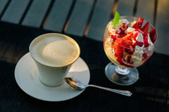 Cappuccino and ice-cream strawberry dessert. White cup of cappuccino coffee and glass bowl of ice-cream with strawberries and whipped cream on dark background Royalty Free Stock Photo