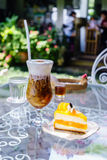 Cappuccino ice and orange cake in coffee shop garden. Cappuccino ice and orange cake on glass table in coffee shop garden Royalty Free Stock Photography