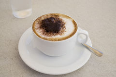 Cappuccino or Italian coffee drink. Cappuccino or Italian coffee with chocolate on top in a white cup and saucer and a water glass at the background Royalty Free Stock Photo