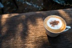 Cappuccino kawa w białej filiżance na drewnianym stole w ogródzie z mo Zdjęcia Stock