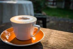 Cappuccino kawa w białej filiżance na drewnianym stole w ogródzie z mo Fotografia Royalty Free