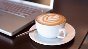 Cappuccino beside laptop on table stock video footage