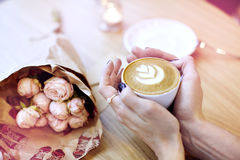 Cappuccino latte coffee in woman hand with heart on top. Flowers on wooden table in modern cafe. St. Valentines celebration concep Royalty Free Stock Photo