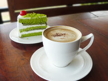 Cappuccino and layer green tea cake. Hot cup of coffee cappuccino and layer green tea cake decorated with red cherry in white plate on wooden table Royalty Free Stock Photo