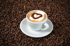 Cappuccino on a lot of coffee beans. Cappuccino with heart on a lot of coffee beans Stock Photos