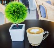 Cappuccino lub latte kawa z zielonym drzewem na stołowy drewnianym Obraz Stock