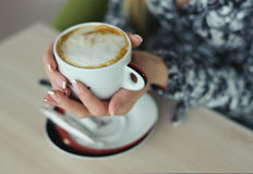 Cappuccino with  in manicured hands of woman Stock Photo