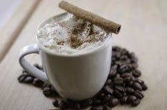 Cappuccino med den kanelbruna pinnen Arkivbild