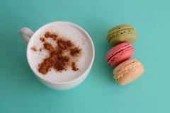 Cappuccino med franska macarons Arkivbild