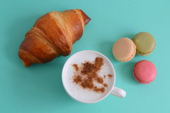Cappuccino med gifflet och macarons Royaltyfri Bild