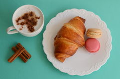 Cappuccino med gifflet och macarons Arkivbilder