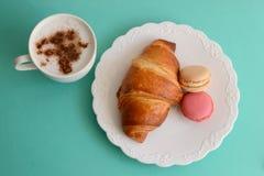 Cappuccino med gifflet och macarons Arkivfoto
