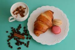 Cappuccino med gifflet och macarons Arkivbild