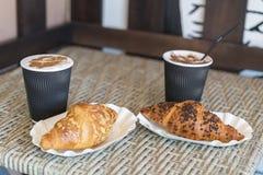 Cappuccino med gifflet Två koppar kaffe med mjölkar skumställningar på en tabell i kafeteria Två koppar kaffe och två giffel Arkivbilder