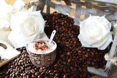 Cappuccino med kaffebönor och rosor arkivfoto
