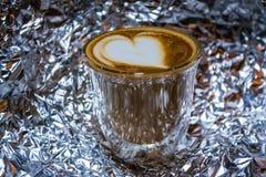 Cappuccino med lattekonst i genomskinligt exponeringsglas med dubbla väggar på bakgrunden från en folie Hjärta Stark drink med ko arkivfoto