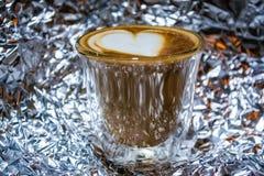 Cappuccino med lattekonst i genomskinligt exponeringsglas med dubbla väggar på bakgrunden från en folie Hjärta Stark drink med ko royaltyfri foto