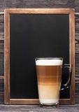 Cappuccino and menu chalkboard. Cappuccino or latte and a chalk board with space for text Stock Image