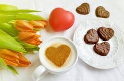 Cappuccino met hartpatroon van kaneel en bloemensamenstelling Royalty-vrije Stock Afbeeldingen