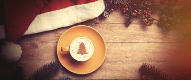 Cappuccino met Kerstmishoed en pijnboom op lijst stock foto