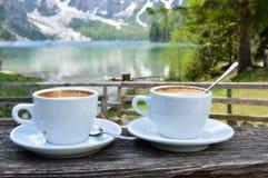 Cappuccino mit dem wunderbaren Hintergrund von See Braies - Dolomit - Italien stockfotografie