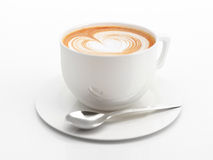 Cappuccino mug close-up, with a heart decorated on top of foam. Royalty Free Stock Image