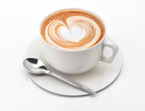 Cappuccino mug close-up, with a heart decorated on top of foam. At white background with clipping path Stock Photos