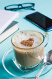 Cappuccino, note books and a phone  on a table Royalty Free Stock Photo