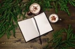 Cappuccino, Notizblock, Fichtenzweige am Abend auf einem hölzernen Hintergrund Stockbild