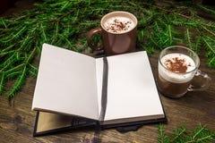 Cappuccino, Notizblock, Fichtenzweige am Abend auf einem hölzernen Hintergrund Stockfotografie