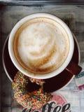Cappuccino och biten munk på ett magasin arkivbilder