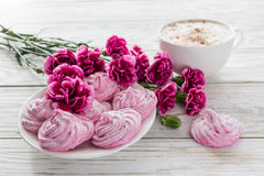 Cappuccino och hemlagad marshmallowefterrätt, rosa nejlikor på trätabellen Arkivbild