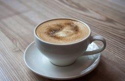 Cappuccino på den ljusa trätabellen arkivfoto