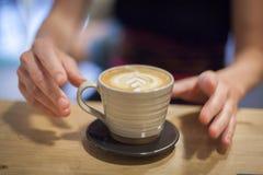 Cappuccino på en trätabell Fotografering för Bildbyråer