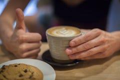 Cappuccino på en trätabell Arkivbilder