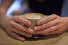 Cappuccino på en trätabell Arkivfoton
