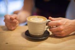 Cappuccino på en trätabell Arkivfoto
