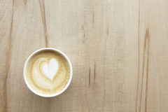 Cappuccino in paper take away cup on light wood table. Cappuccino with heart in paper take away cup on light wood table. From above Stock Image