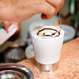 Cappuccino preparation. A barman is preparing a cappuccino Royalty Free Stock Photography