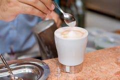 Cappuccino preparation. A barman is preparing a cappuccino Stock Image