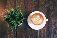 Cappuccino quente em uma tabela de madeira em uma cafetaria Foto de Stock Royalty Free