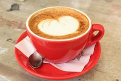 Cappuccino in red mug with foam heart stock image