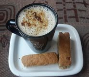 Cappuccino and Rusks. Cappuccino sprinkled with hot chocolate served with rusks Royalty Free Stock Photos